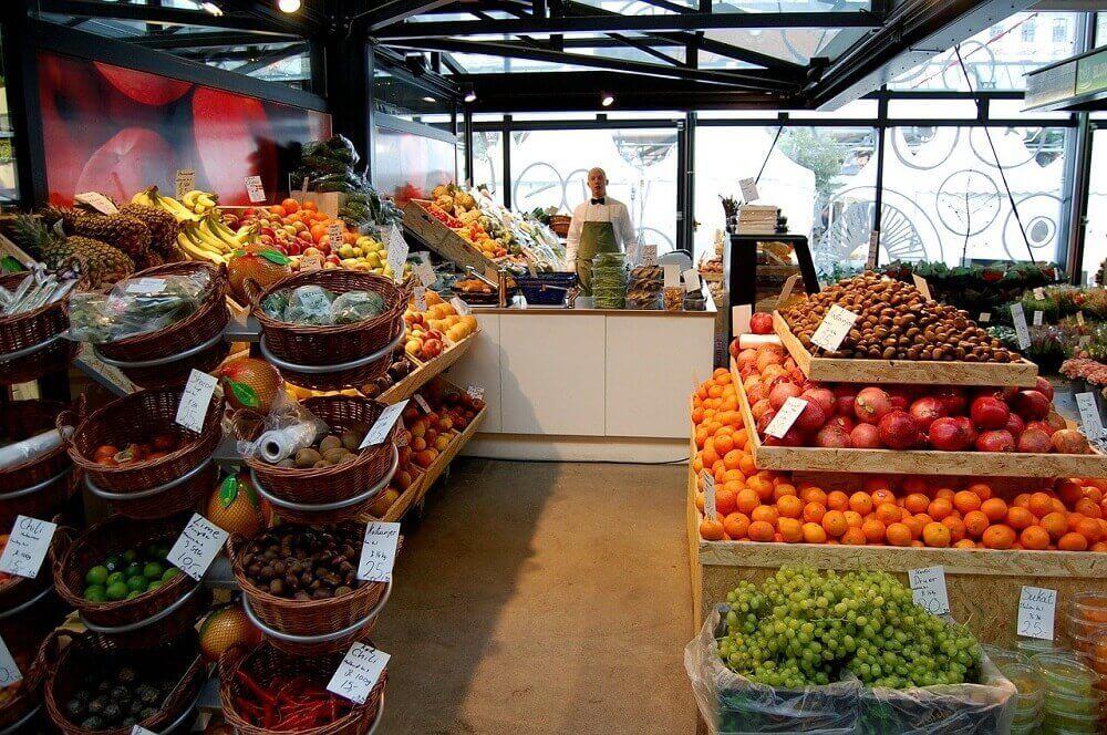 Продавец у прилавка в овощном магазине